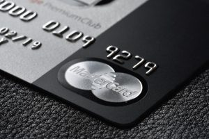 Black and silver premium credit card MasterCard Black Edition on the black leather background.